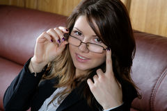 The girl in glasses and  business suit on a sofa Stock Image