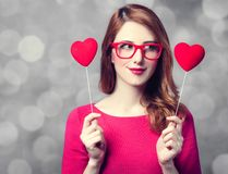 Girl in glasses and dress with two heart shapes royalty free stock image