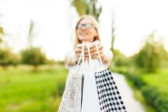 girl with glasses, dressed in a white t-shirt, holding a purchase while in the Park stock photos