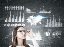 Girl in glasses and graphs on blackboard Stock Photography