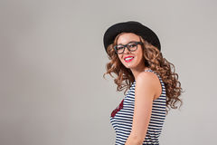 Girl in glasses and hat. The girl in glasses and hat on gray studio background Royalty Free Stock Photography