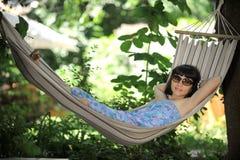 Girl in glasses having rest in a hammock Royalty Free Stock Image
