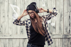 Girl in glasses, headphones and black beanie Stock Images