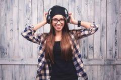 Girl in glasses, headphones and black beanie Stock Image