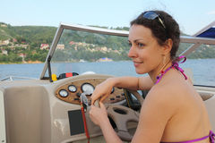 Girl in glasses at helm of cutter Royalty Free Stock Image