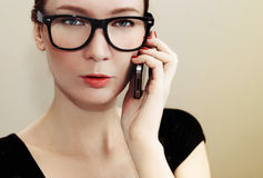 Girl with glasses holding a mobile phone Royalty Free Stock Photo