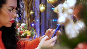 Girl in glasses holding smartphone. Young serious curly woman in glasses, a red sweater and with red lips with a phone on a background of Christmas decor. Girl stock footage
