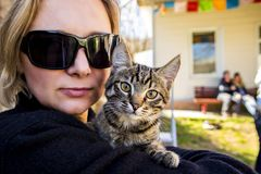 The girl in glasses holds a striped kitten. In her arms stock photo