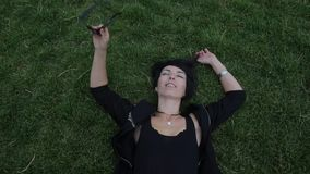 Girl lying on the green grass. Girl in glasses lies on green grass stock footage