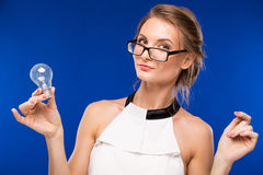 Girl in glasses with a light bulb in his hands Stock Images