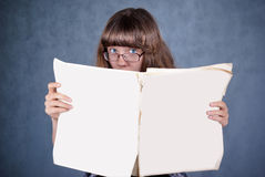 Girl in glasses looking over newspaper. Girl in glasses and black hat reading newspaper and looking over Stock Images
