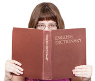 Girl with glasses looks over English Dictionary Royalty Free Stock Photo