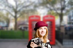 Girl in glasses making photo on London street Stock Photography
