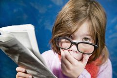 Girl with Glasses and a Newspaper Royalty Free Stock Image