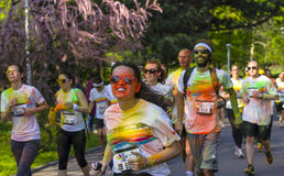 Girl with glasses and orange powder running. Smiling girl wearing glasses and covered in colored powder running alongside other people at the Color Run event on Stock Photos