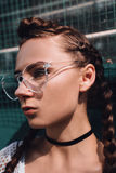 Girl in glasses with pigtails outdoors. Beautiful fashion girl in glasses Stock Photos