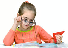 Girl with glasses reading book. A young girl sitting at a desk or table, reading a book and playing with over sized glasses that exaggerate her eyes.  White Royalty Free Stock Photo
