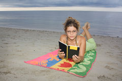 Girl with glasses reading a book in the beach. Laying on a towel Stock Photography