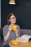 Girl in glasses reading a book in a coffee shop Stock Photography