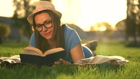 Girl in glasses reading book lying down on a blanket in the park at sunset. Traditional reading stock video footage