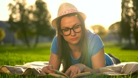 Girl in glasses reading book lying down on a blanket in the park at sunset. Traditional reading stock footage
