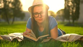 Girl in glasses reading book lying down on a blanket in the park at sunset. Traditional reading stock video