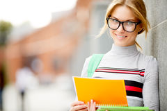 Girl with glasses reading book outdoors Royalty Free Stock Image