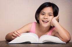 Girl with glasses reading and having fun. Royalty Free Stock Photography