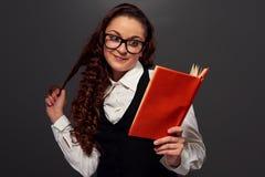 Girl in glasses reading a romance. Smiley girl in glasses reading a romance over dark background Stock Photo