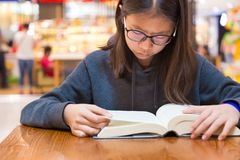 Girl with glasses reading a thick fiction story book at a table. Inside a public place with blurred shops background, good for education or using free time Stock Images