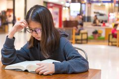 Girl with glasses reading a thick fiction story book at a table. Inside a public place with blurred shops background, good for education or using free time Royalty Free Stock Photography