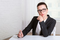 Girl in glasses resting her hand on her chin Royalty Free Stock Images