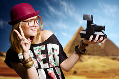 Girl in glasses with retro camera on Egypt pyramid. Picture of joyfull woman in hipster glasses and pot hat with vintage camera. Young traveler smiling on Egypt Royalty Free Stock Images
