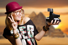 Girl in glasses with retro camera on Egypt pyramid. Picture of joyfull woman in hipster glasses and pot hat with vintage camera. Young traveler smiling on Egypt Stock Photos