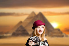 Girl in glasses with retro camera on Egypt pyramid. Picture of joyfull woman in hipster glasses and pot hat with vintage camera. Young traveler smiling on Egypt Stock Photo