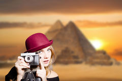 Girl in glasses with retro camera on Egypt pyramid. Picture of joyfull woman in hipster glasses and pot hat with vintage camera. Young traveler smiling on Egypt Royalty Free Stock Photos
