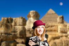 Girl in glasses with retro camera on Egypt pyramid. Picture of joyfull woman in hipster glasses and pot hat with vintage camera. Young traveler smiling on Egypt Royalty Free Stock Photography
