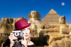 Girl in glasses with retro camera on Egypt pyramid. Picture of joyfull woman in hipster glasses and pot hat with vintage camera. Young traveler smiling on Egypt Stock Images