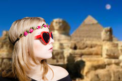 Girl in glasses with retro camera on Egypt pyramid. Picture of joyfull woman in hipster glasses and pot hat with vintage camera. Young traveler smiling on Egypt Royalty Free Stock Photo