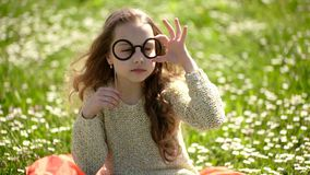 Girl with glasses sits in chamomile field on a sunny day. Sweet little girl outdoors. Happy girl portrait. Kids fashion. And accessory concept. Portrait of stock video