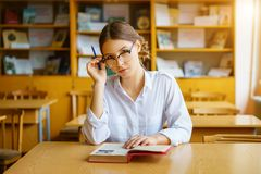 Girl with glasses sitting at a table with a book in the classroom, holding a pencil in his hand, thoughtful look royalty free stock image