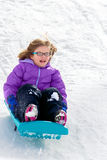 Girl in Glasses Sledding. A happy girl sleds down a snowy hill. Her sled is backwards, but she doesn't care. Her hair is blowing in the wind and her expression Royalty Free Stock Photography