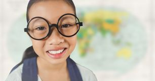 Girl with glasses smiling against blurry map Stock Images