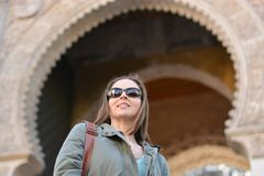 The girl with glasses smiling in front of the city gate royalty free stock image