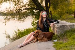 Girl in glasses is smiling at her pet in the summer in the park stock images