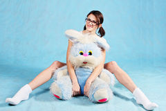 The girl in glasses with a soft toy rabbit. Stock Photography