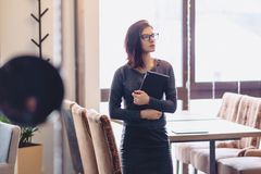 The girl in the glasses is standing with a tablet at the bars. At the cafe Royalty Free Stock Photography