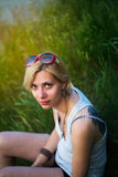 Girl with glasses. Girl in sunglasses sitting in grass in sunny summer day Stock Photos