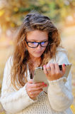 Girl in glasses with a tablet in hands in park Royalty Free Stock Photo