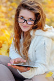 Girl in glasses with a tablet in hands in a park in autumn Stock Image